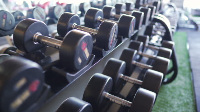 dolly shot dumbbells in empty gym. - exercise machine stock videos & royalty-free footage