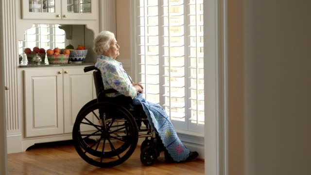 dolly shot elderly person in a wheelchair - loneliness stock videos and b-roll footage