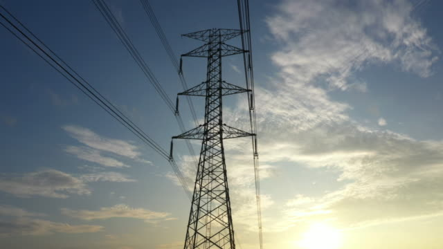 dolly shot electricity pylons with sunrise - elettricità video stock e b–roll