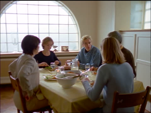 dolly shot family eating dinner + talking around dining room table - meal stock videos & royalty-free footage