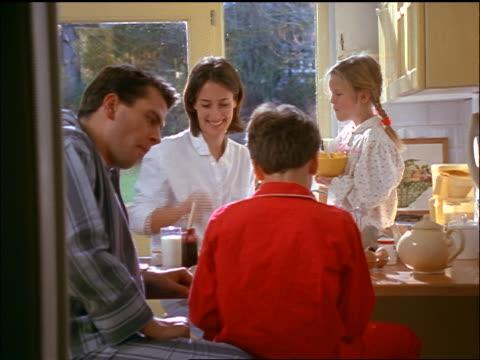 dolly shot family in pajamas eating breakfast + talking at kitchen counter - tvåföräldersfamilj bildbanksvideor och videomaterial från bakom kulisserna