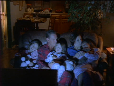 dolly shot family in pajamas sitting on couch watching TV / three daughters sleeping