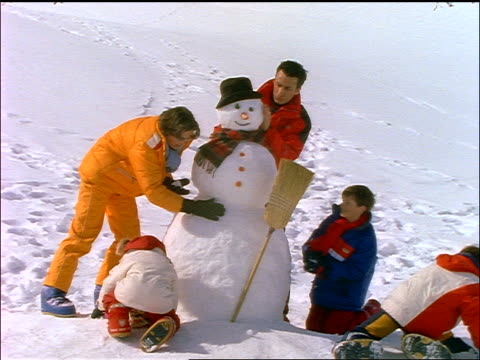 dolly shot family making snowman in snow - making a snowman stock videos & royalty-free footage