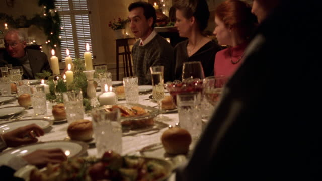 Dolly shot family sitting at Christmas dinner table and cheering as woman brings in roast turkey