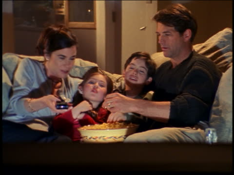 vídeos de stock e filmes b-roll de dolly shot family sitting on couch eating popcorn + watching (offscreen) television - 1990 1999