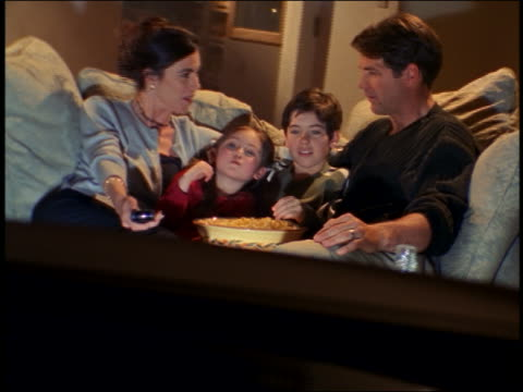 vidéos et rushes de dolly shot family sitting on couch eating popcorn + watching (offscreen) television - 1990 1999