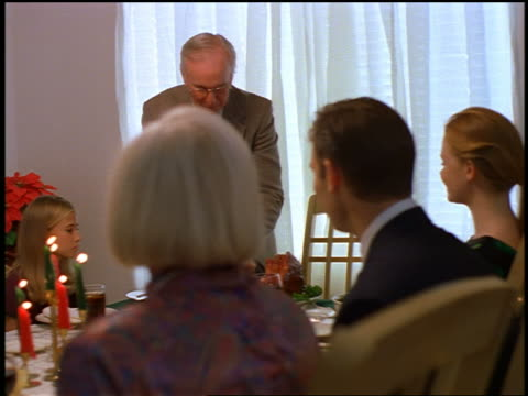 dolly shot family watching as senior man cuts ham at dining room table / christmas - meal stock videos and b-roll footage
