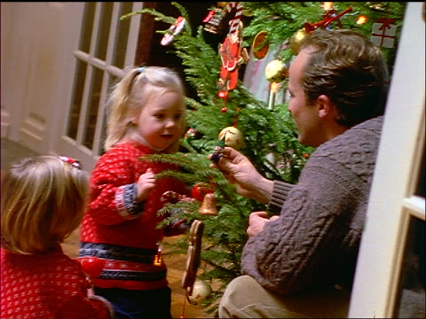 dolly shot father + two small blonde girls decorating christmas tree - decorating the christmas tree stock videos & royalty-free footage