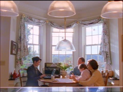 dolly shot female financial advisor sitting at kitchen table talking to family - rättsväsendet bildbanksvideor och videomaterial från bakom kulisserna