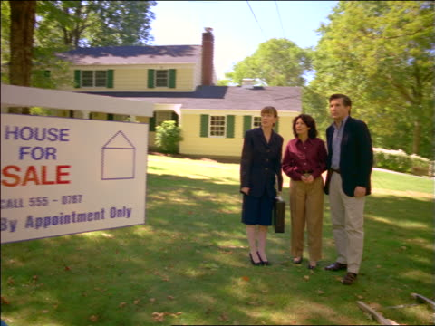 """dolly shot female real estate agent showing house + grounds to couple / """"house for sale"""" sign in foreground - estate agent sign stock videos & royalty-free footage"""