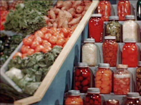 1946 dolly shot from display of vegetables to display of jarred fruits and vegetables at State Fair / indust /