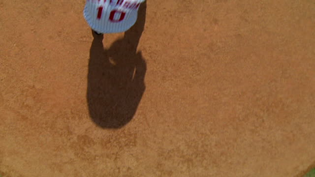 overhead dolly shot from shadow to pitcher winding up + pitching baseball - 野球用グローブ点の映像素材/bロール