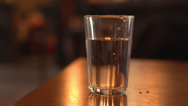 dolly shot glass of water with orange theme copy space - volume fluid capacity stock videos & royalty-free footage