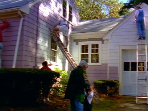 dolly shot grandmother walking toddler through group of people painting small house exterior lavender