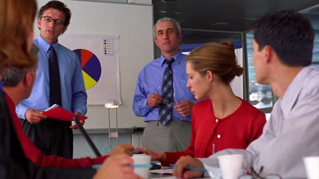 dolly shot group of businesspeople talking + looking at charts in meeting - training course stock videos & royalty-free footage