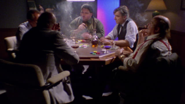 stockvideo's en b-roll-footage met dolly shot group of men sitting around table playing poker, smoking cigars + drinking alcohol - gokken