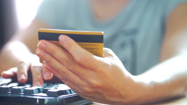 stockvideo's en b-roll-footage met dolly schoot handen te typen toetsenbord van de computer en een creditcard voor online winkelen thuis te houden. - gereedschap