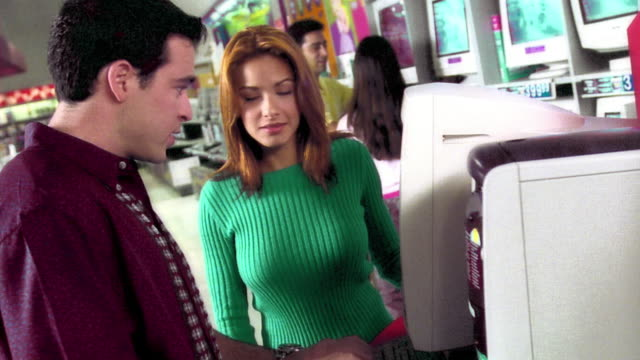 ms dolly shot hispanic couple looking at, discussing, + trying computer on display in store - electronics store stock videos & royalty-free footage