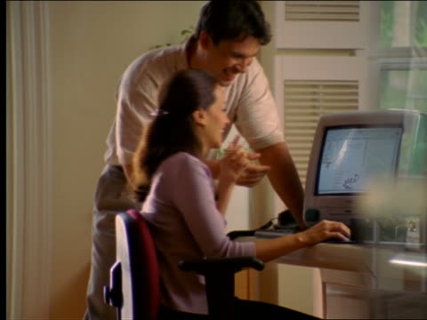 dolly shot Hispanic couple talking + working on computer (Computer)