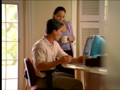 dolly shot hispanic man typing on computer (computer) with hispanic woman looking on - 中年カップル点の映像素材/bロール