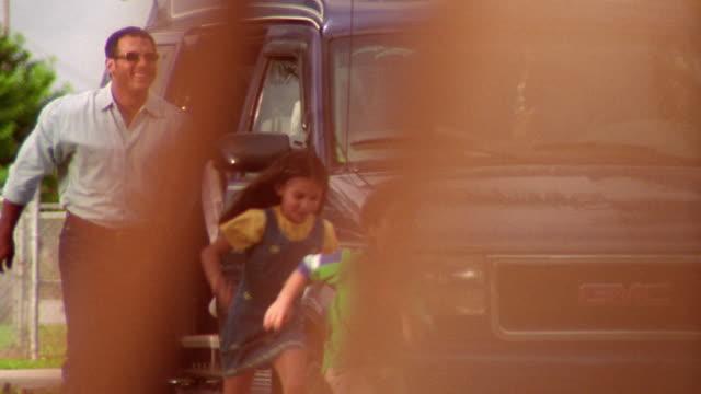 dolly shot hispanic man with children exiting minivan + running to hug senior man in cowboy hat - grandparent stock videos & royalty-free footage