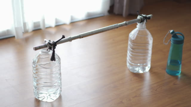 dolly shot homemade dumbbell/barbell from plastic water gallon. - fatto in casa video stock e b–roll