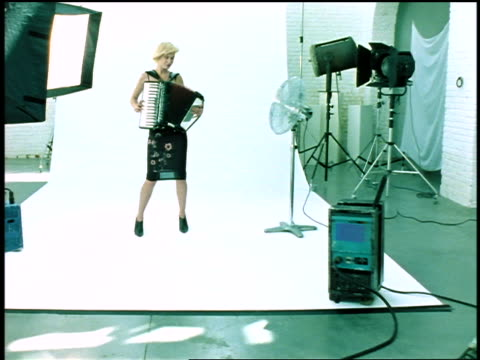 dolly shot in blonde woman playing accordian standing against white background in studio by fan + lights