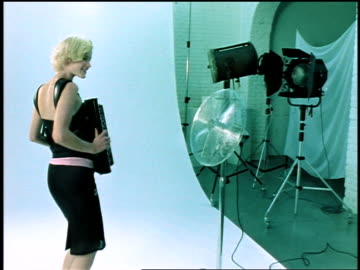 dolly shot in blonde woman playing accordian standing against white background in studio by fan + lights - 1999 stock videos & royalty-free footage
