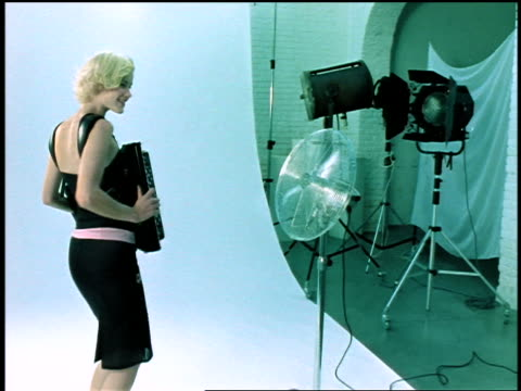 vidéos et rushes de dolly shot in blonde woman playing accordian standing against white background in studio by fan + lights - 1990 1999