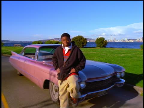 stockvideo's en b-roll-footage met dolly shot in + out black teen boy sitting on hood of 1960 pink cadillac on road / city in far background - alleen één tienerjongen