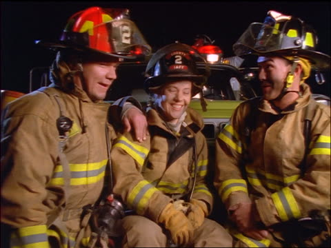 dolly shot in PORTRAIT three smiling firefighters (1 woman) talking + sitting on front of truck at night