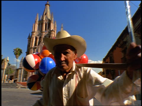 dolly shot in to close up senior Mexican man holding stick with inflatable balls attached in front of cathedral
