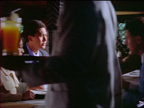 dolly shot in to Indonesian couple in restaurant with Caucasian businessman / men shake hands / Jakarta