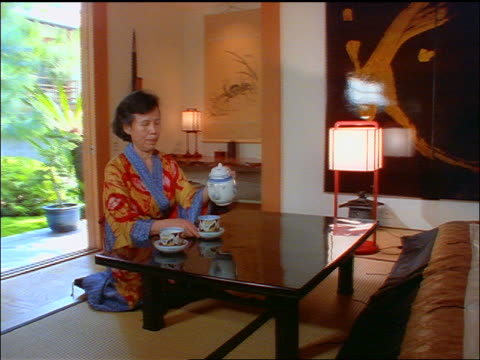 dolly shot in to middle-aged asian woman on tatami mat pouring tea + sipping it - tatami mat stock videos and b-roll footage