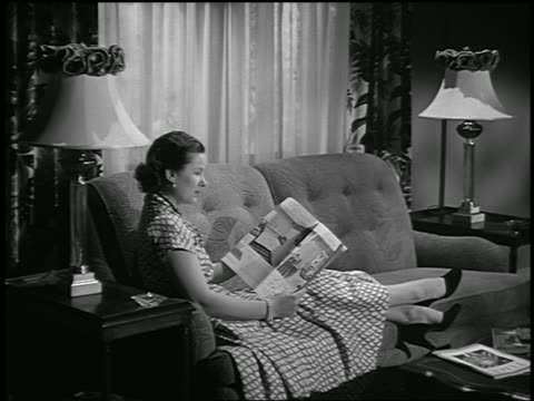 B/W 1950 dolly shot in woman sitting on sofa in living room reading magazine / industrial