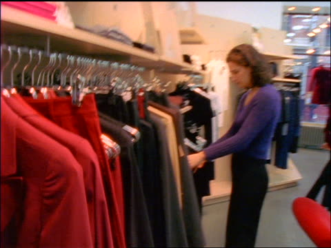 dolly shot indecisive woman looking at clothing on racks in soho store / nyc - clothes rail stock videos & royalty-free footage