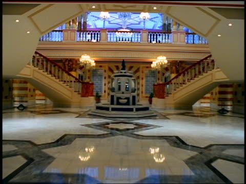vídeos y material grabado en eventos de stock de dolly shot into lobby of ornate palace with staircases + balconies / tilt up to ceiling / istanbul, turkey - palacio interior