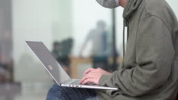 Dolly shot IT support worker sitting with a laptop outdoors in a park.(Close up hand