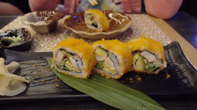 vídeos de stock, filmes e b-roll de 4k: dolly tiro japonês maki sushi ou sushi tempura de camarão. - lunch
