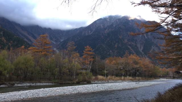 vídeos de stock, filmes e b-roll de dolly tiro kamikochi mountain view com rio e árvore na província de nagano nevoeiro, japão - estampa de folha