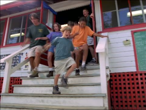 dolly shot large group of children + camp counselors running through doors of building + down stairs - summer camp stock videos & royalty-free footage