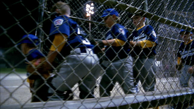 Dolly shot Little League team running onto field / through fence / Seattle, Washington