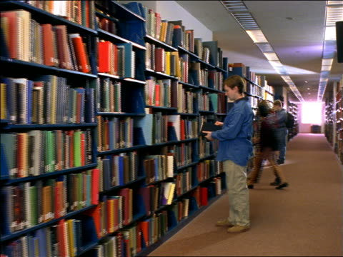 vidéos et rushes de dolly shot male college student examining book + placing it in bookshelf in school library / boston, ma - rayonnage de livre