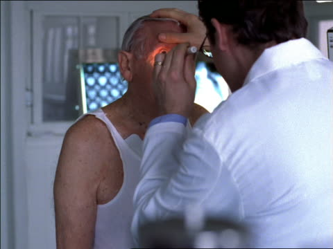 dolly shot male doctor examining eyes of senior male patient in office