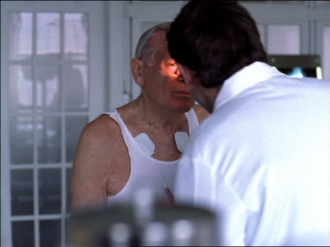 dolly shot male doctor examining senior male patient in office / checking eyes with flashlight