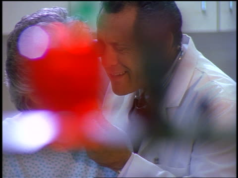 dolly shot male doctor looking in eyes + ear of senior woman in examining room - examination gown stock videos & royalty-free footage