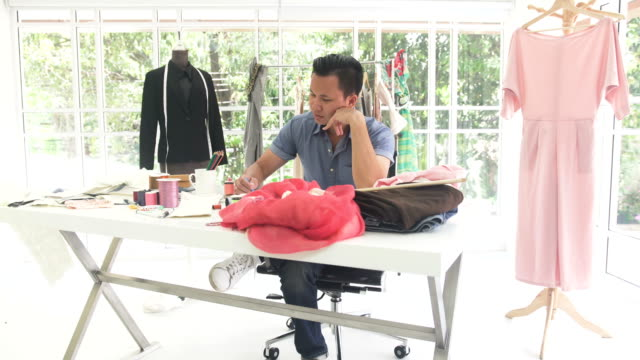 vídeos de stock e filmes b-roll de dolly shot:  male fashion designer working in home office - 30 34 years