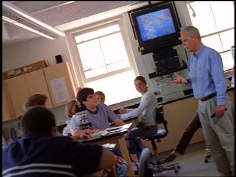 CANTED dolly shot male science teacher talking with students in high school laboratory
