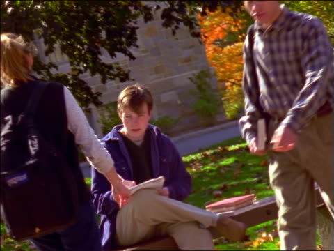 vídeos de stock e filmes b-roll de dolly shot male student sitting on bench on college campus + writing in notebook / greeting friends / boston - sentar se