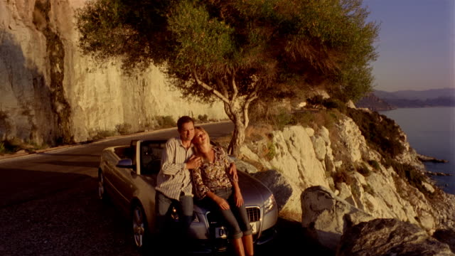 dolly shot man and woman sitting on hood of convertible looking at view / woman resting head on man's shoulder / man caressing woman's arm / corsica - 年の差カップル点の映像素材/bロール